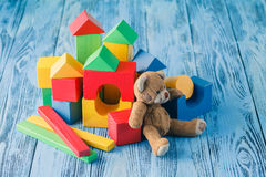 Shot of pile of various wooden blocks and toy bear Royalty Free Stock Photos