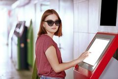 Shot of pretty Caucasian woman in trendy sunglasses, poses near ATM machine with blank screen, needs to withdraw money, stands in stock image