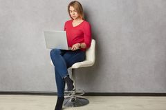shot of pretty serious blonde woman focused in laptop computer, sits at white armchair, dressed in red jumper and jeans, stock photography