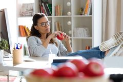 Pretty young business woman eating red apple while taking a break in the office. Shot of pretty young business woman eating red apple while taking a break in the royalty free stock photo