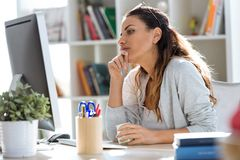 Pretty young business woman eating yogurt while working with computer in the office. Shot of pretty young business woman eating yogurt while working with royalty free stock photo