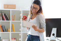 Pretty young business woman using her digital tablet while eating red apple in the office. Shot of pretty young business woman using her digital tablet while stock images
