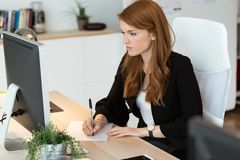 Pretty young business woman using her laptop in the office. Stock Photo