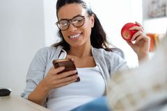Pretty young business woman using her mobile phone while eating red apple in the office. Shot of pretty young business woman using her mobile phone while eating stock photos