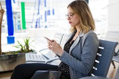 Pretty young business woman using her mobile phone in the train station. Royalty Free Stock Images