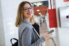Pretty young business woman using her mobile phone in the train station. Royalty Free Stock Image