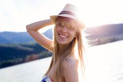 Pretty young woman looking at camera on pier near to lake. Royalty Free Stock Photography