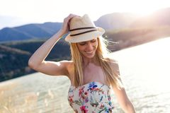 Pretty young woman posing and relaxing on pier near to lake. Stock Photo