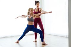 Pretty young yoga instructor helping her student in a yoga session at home. Virabhadrasana II pose. stock image