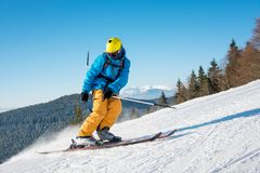 Skier riding in the mountains on a sunny winter day. Shot of a professional skier riding the slope on a beautiful winter day copyspace ski resort recreation Stock Image