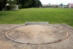 Shot put circle from behind. A local high schools shot put circle looking from behind out on to a grass field Stock Images