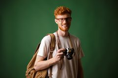 Shot of readhead bearded hipster with retro camera and backpack Royalty Free Stock Photography