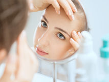 Shot of a reflection of a young woman examining her face Royalty Free Stock Photos