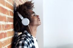 Relaxed afro-american young man listening to music with headphones leaning on stone wall at home stock images