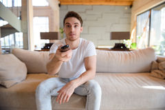 Shot of remote controller. Closeup shot of remote controller in man`s hand while he sitting on couch Stock Photo