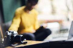 Shot of retro vintage camera. On frontage standing on wooden table in modern studio with skilled male photographer on blurred background preparing for making Royalty Free Stock Photo