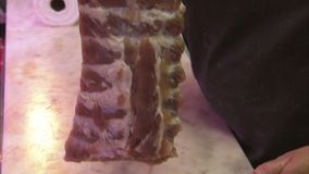 Rib part of a meat. A shot of a rib part meat of a pig in a supermarket. A man with a black apron is holding the meat stock video footage
