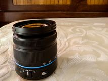 A shot of a Samsung NX series lens with a blue strip on a white fabric royalty free stock image
