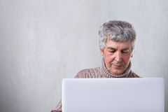 A shot of senior male having gray hair and wtinkles on the face looking into the screen of his laptop reading a book online. A han royalty free stock photography