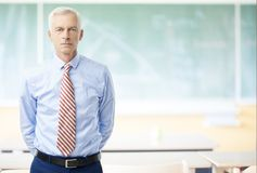 Male teacher in the school. Shot of a senior male teacher standing in the lecture hall in front of the chalkboard Royalty Free Stock Image