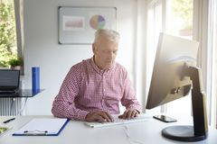 Senior buisnessman working in the office royalty free stock image