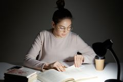 Shot of serious young Caucasian woman has focused look into textbook, finds necessary information, holds pencil, wears round big s. Pectacles, sits in darkness stock photo