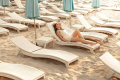 Shot of sexy woman enjoying rest on sunbed at beach Stock Photos