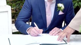 Signing of marriage register or guest book. Shot of signing of marriage register or guest book stock footage