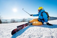 Skier resting on top of the mountain. Shot of a skier sitting on the ski slope taking a selfie using selfie stick resting relaxing extreme recreation active Stock Image