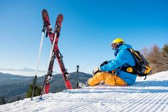 Skier resting on top of the mountain. Shot of a skier sitting on slope near his skiing equipment relaxing enjoying beautiful snowy mountains view people living Royalty Free Stock Image