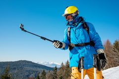 Male skier using selfie stick taking photos while skiing. Shot of a skier in winter clothing taking a selfie using monopod for his camera. Blue sky and winter Stock Image