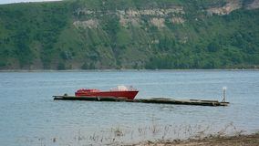 Shot of small red rescue boat on the river against mountain with forest stock video