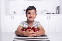 Shot of a smiling boy sitting in the kitchen and hugging a large bowl of strawberries and cherries stock image