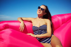 A shot of smiling skinny brunette leaning elbow on a pink inflat Stock Photography