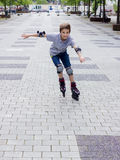 Shot of smiling sliding rollerskater in protection. Kit Royalty Free Stock Images