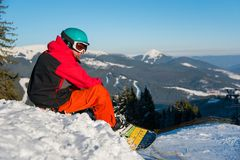 Snowboarder resting on top of the mountain. Shot of a snowboarder enjoying beautiful view of snowy mountains, winter ski resort, relaxing on the edge of a slope Stock Images