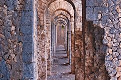 Roman ruins arches forming a hallway in Italy near the Mediterranean Sea. Shot of some arches in a mountain top fort near Gaeta, Italy in the Summer royalty free stock photo