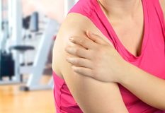 My shoulder hurts. Shot of a sportswoman with a shoulder injury at the gym club stock photos