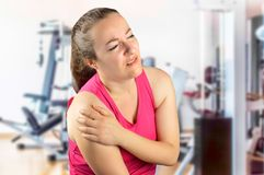 My shoulder hurts. Shot of a sportswoman with a shoulder injury at the gym club royalty free stock photography