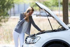 Stressed young woman calling for assistance after breaking down car in the street. royalty free stock photo