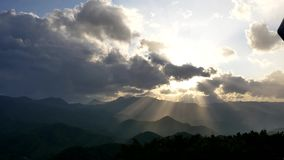 Shot of the sun ray breaking through cloud from the top of mountain moiwa, hokkaido, japan. Wide shot of the sun ray breaking through cloud from the top of stock footage