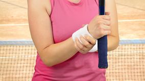 Tennis sportwoman with wrist pain. Shot of a tennis player with a wrist injury on a clay court Stock Photos