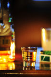 Shot of tequila in an environment. Shot of tequila surrounded by a beverage,the bottle and cigarettes Stock Image