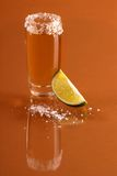 Shot of tequila with lime. A shot of tequila with a salted rim and a lime on reflective gold surface Stock Image