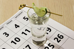 Shot of tequila with a slice of lime on the calendar at friday. Stock Photography