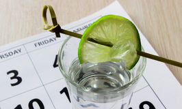 Shot of tequila with a slice of lime on the calendar at friday. royalty free stock image