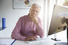 Senior businessman looking thoughtfully while working on compute stock photo