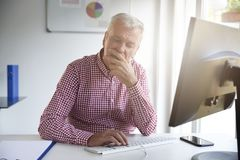 Senior businessman looking thoughtfully while working on compute stock images