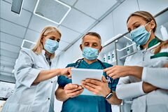 All research in a small gadget. Shot of three medical professionals talking using a digital tablet together at the hospital
