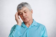 Shot of tired elderly male pensioner, keeps eyes closed, hand on temple, wears formal blue shirt, has headache, poses against whit royalty free stock photography